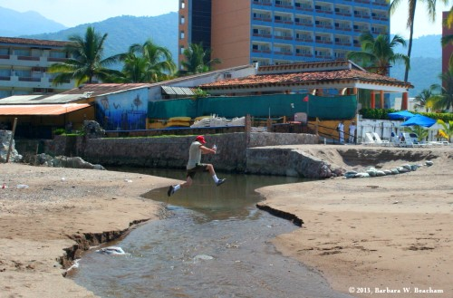 Jumping a stream on the beach at Puerta Vallarta