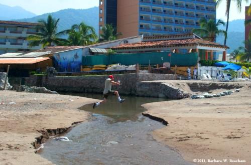 Jumping a stream on the beach at Puerta Vallarta