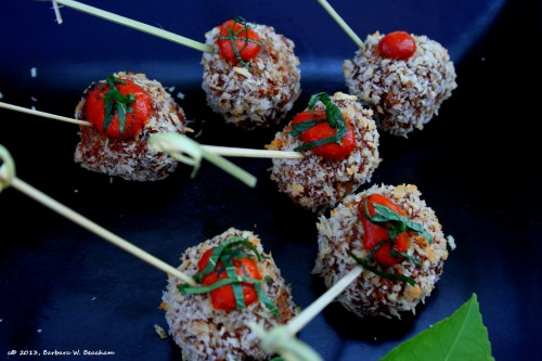 Panko encrusted lamb meatballs topped with a red pepper sauce and fresh mint